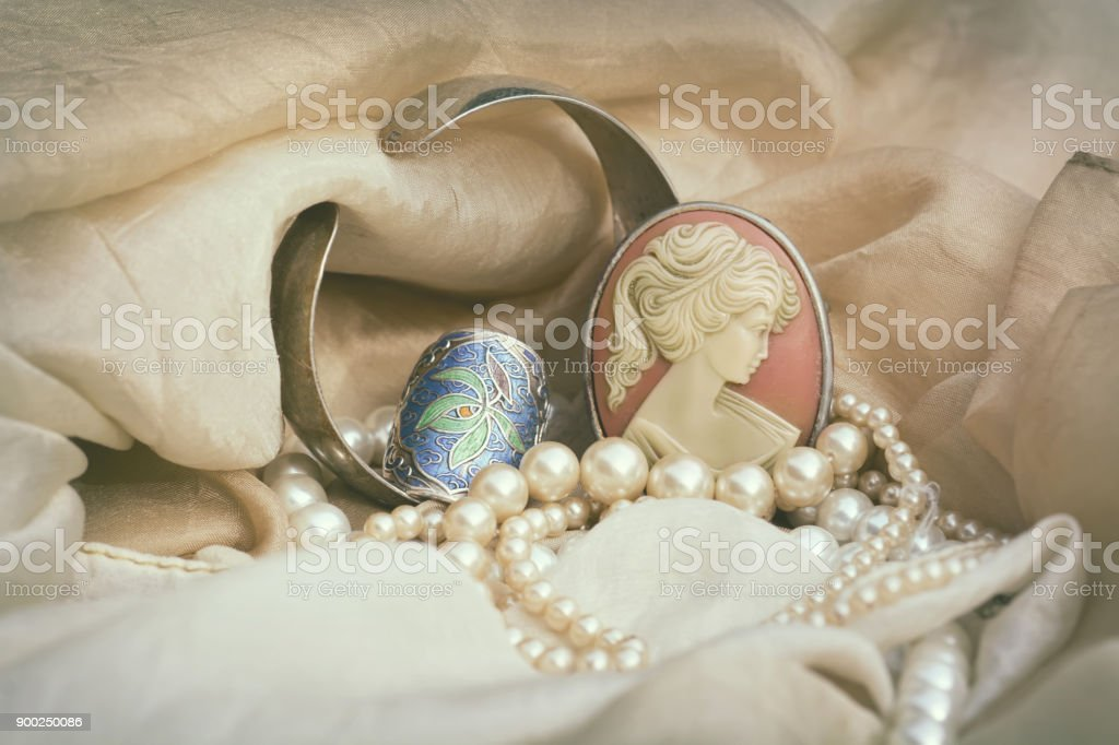 Woman's Jewellery. Vintage jewellery with cameo brooch, silver ring and genuine pearls stock photo