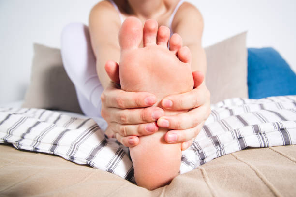 Woman's leg hurts, pain in the foot, massage of female feet stock photo