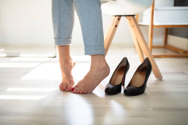 woman's leg near high heels - callo foto e immagini stock