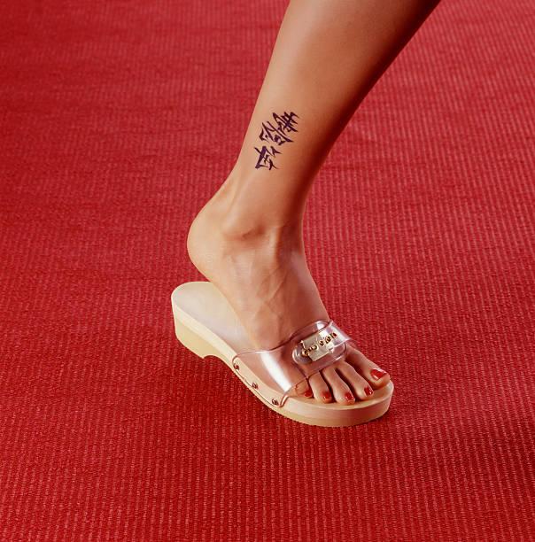 frau beine mit chinesischen tätowierung mit einem holz-sandale - chinesische zeichen tattoos stock-fotos und bilder