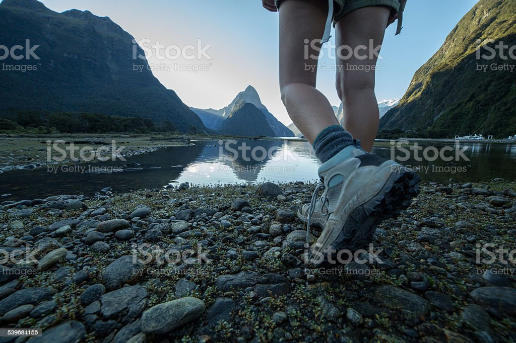 Woman's legs and hiking boots standing on rocky trail stock photo