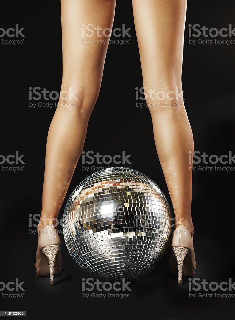Woman's legs backwards on either side of disco ball stock photo