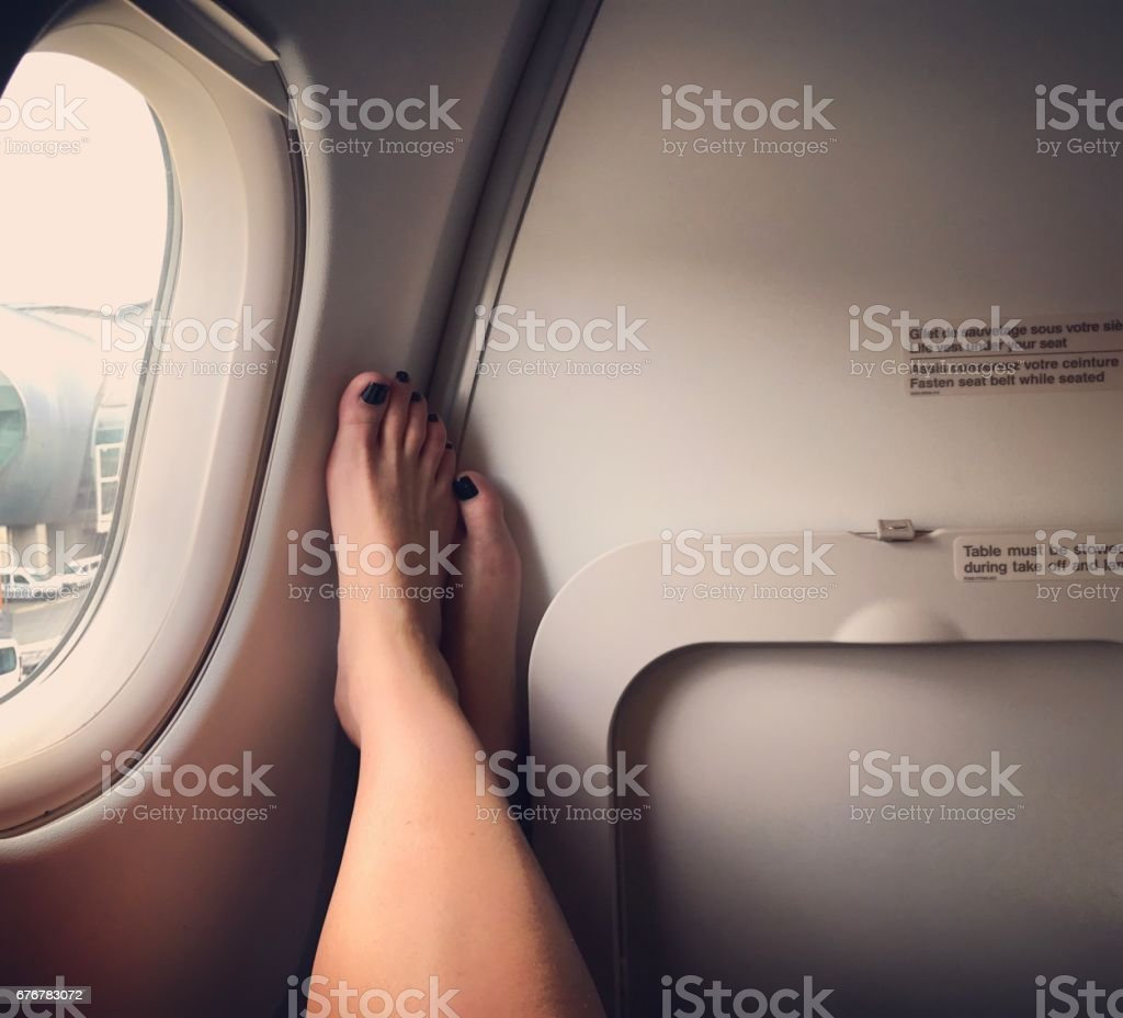 Woman's legs by the airplane window stock photo