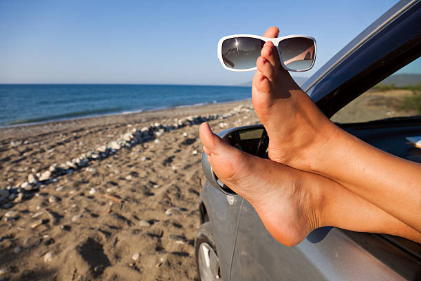 Woman's legs dangling out a car window stock photo