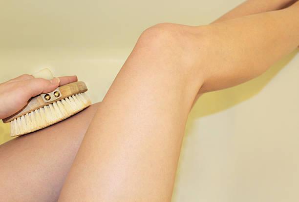frau beine trocken körper-peeling - peeling bürste stock-fotos und bilder