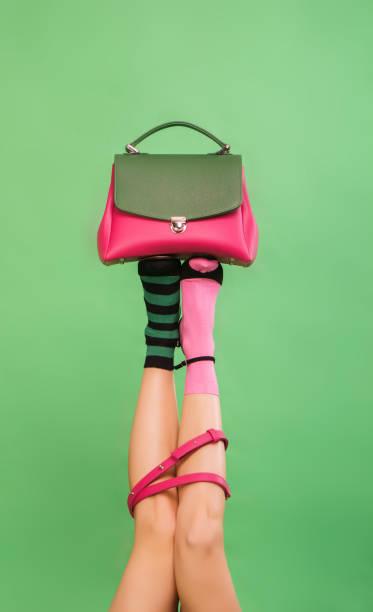 frauenbeine holding handtasche auf grünem hintergrund - leder handtaschen damen stock-fotos und bilder