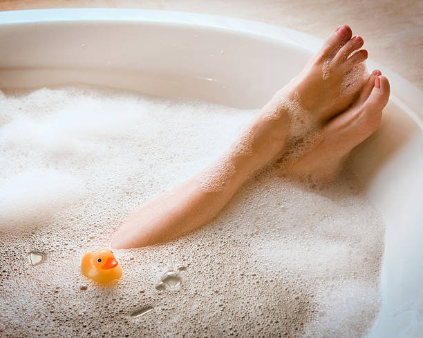 Woman's Legs in Bubble Bath with Ducky Woman in bathtub. Bubble Bath. Horizontal shot. bathtub stock pictures, royalty-free photos & images