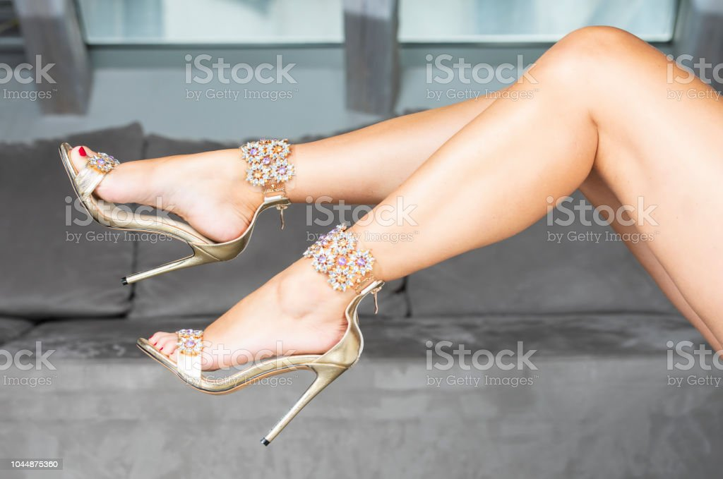 Woman´s legs in golden glamour High Heels sandals stock photo