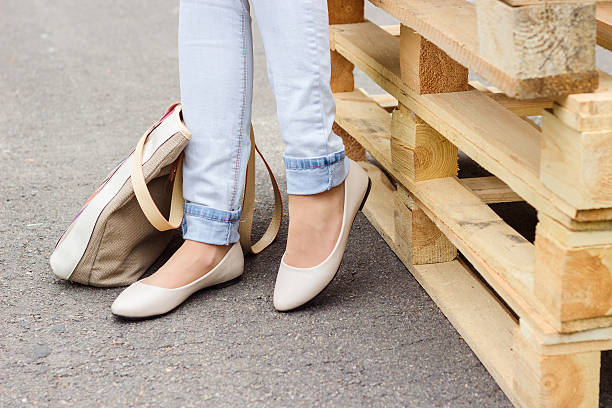 woman's legs in jeans and flat shoes - flat shoe stock photos and pictures