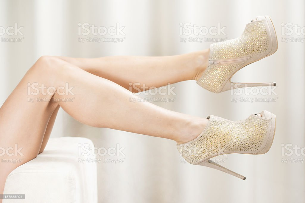 Woman´s legs in luxurious golden High Heels Ankle Boots stock photo