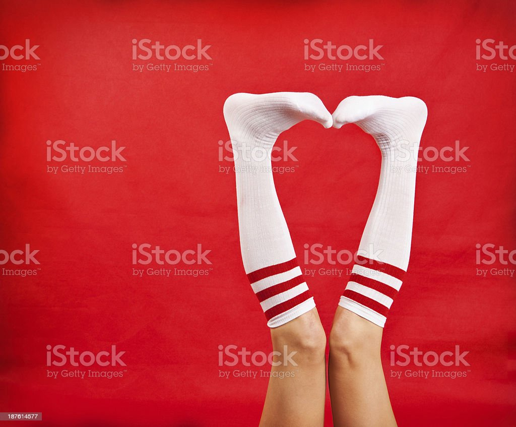 Woman's Legs In Tube Socks Making Heart Shape stock photo