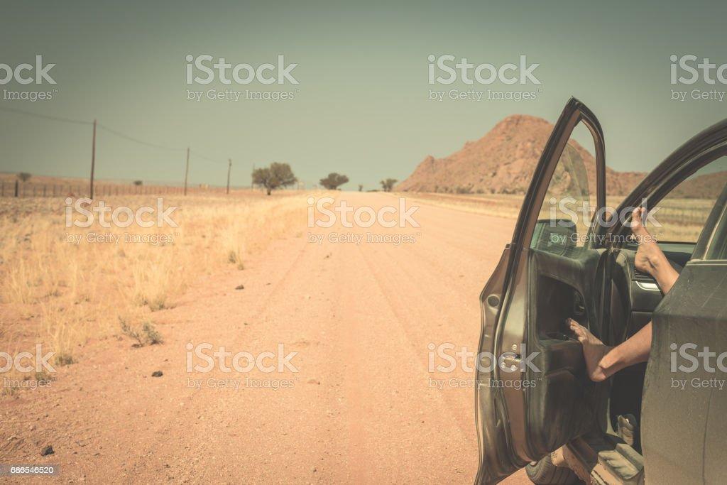 Woman's legs leaning out from car zbiór zdjęć royalty-free