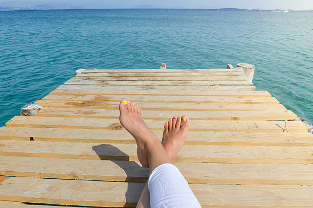 womans legs on a dock while relaxing on seaside - woman leg beach pov stock photos and pictures