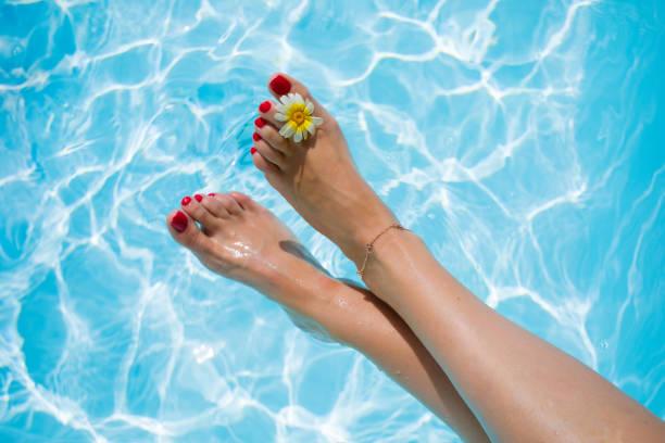 frauenbeine auf den swimmingpool - wachsblume stock-fotos und bilder