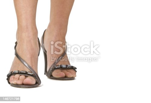 \r\nIsolated woman's legs in higheels sandals.Natural look of the skin.Copyspace for your message in the right part of the image.Selective focus on the right foot.