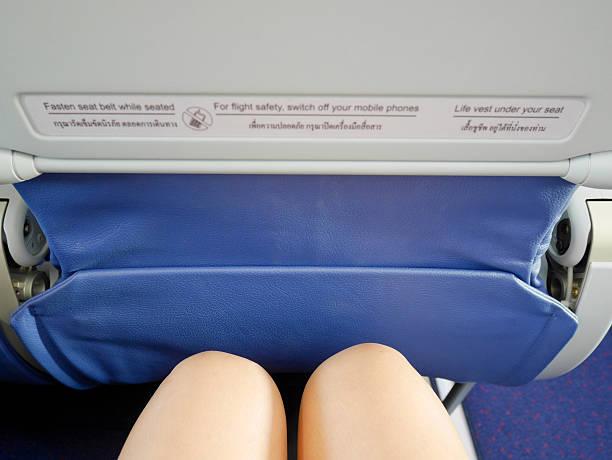 woman's legs sitting in a plane - étroit photos et images de collection