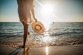 istock Woman's legs splashing water on the beach 1255493335