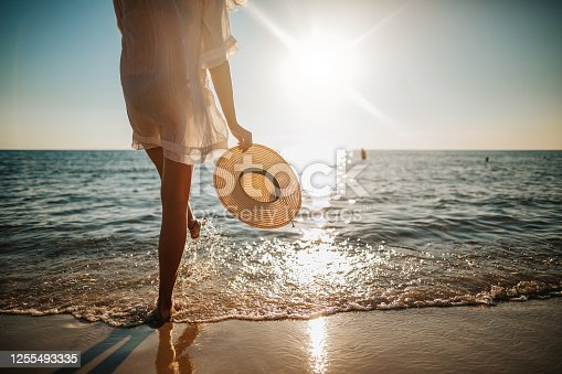 istock Woman's legs splashing water on the beach 1255493335