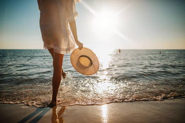 las piernas de la mujer salpicando agua en la playa - playa fotografías e imágenes de stock