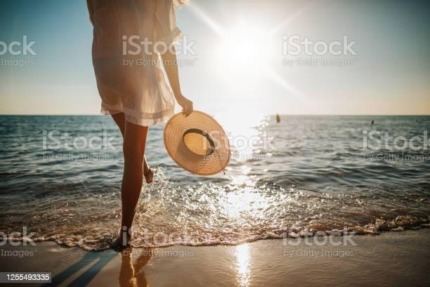 Photo of Woman's legs splashing water on the beach