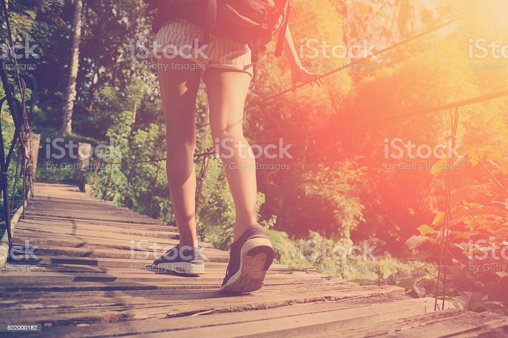 Woman's legs walking across bridge stock photo