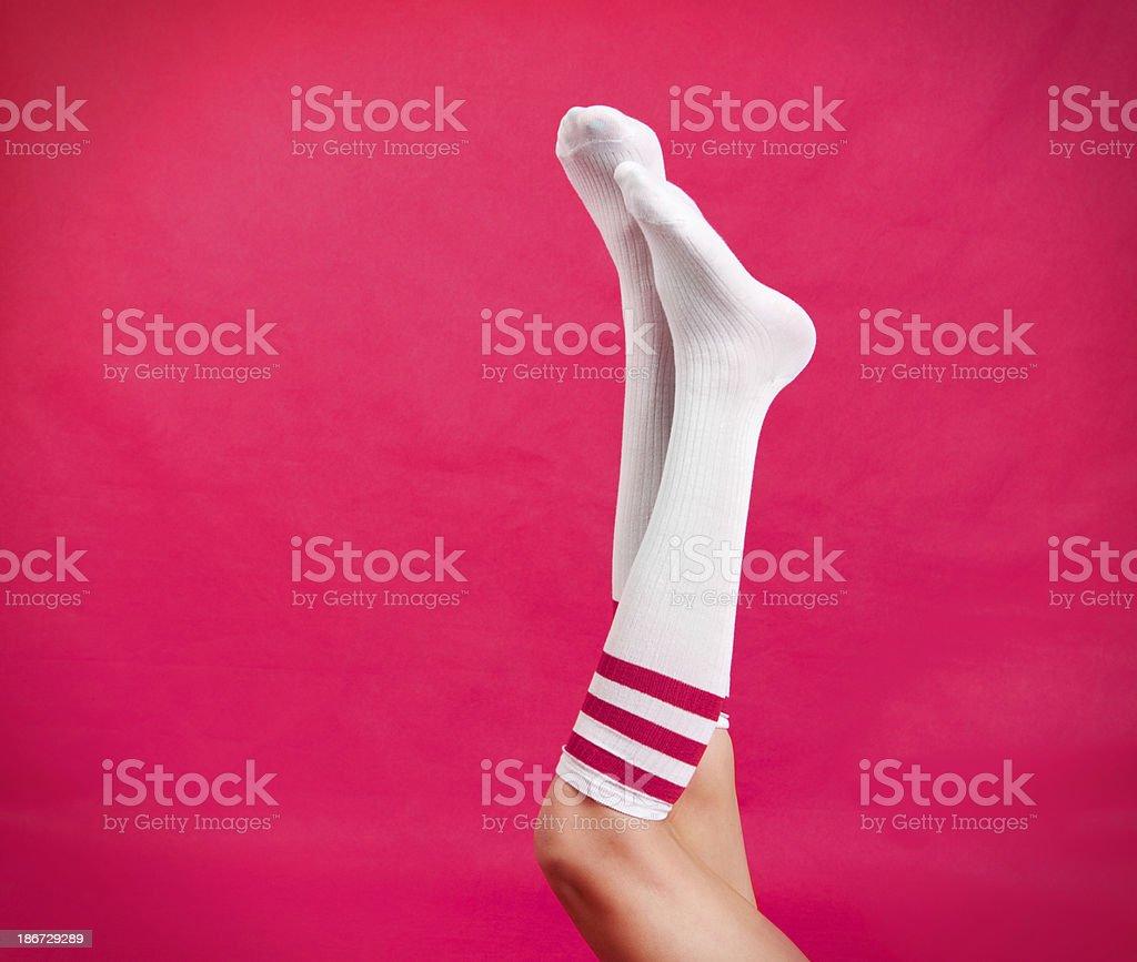 Woman's Legs Wearing Pink Striped Knee Socks stock photo