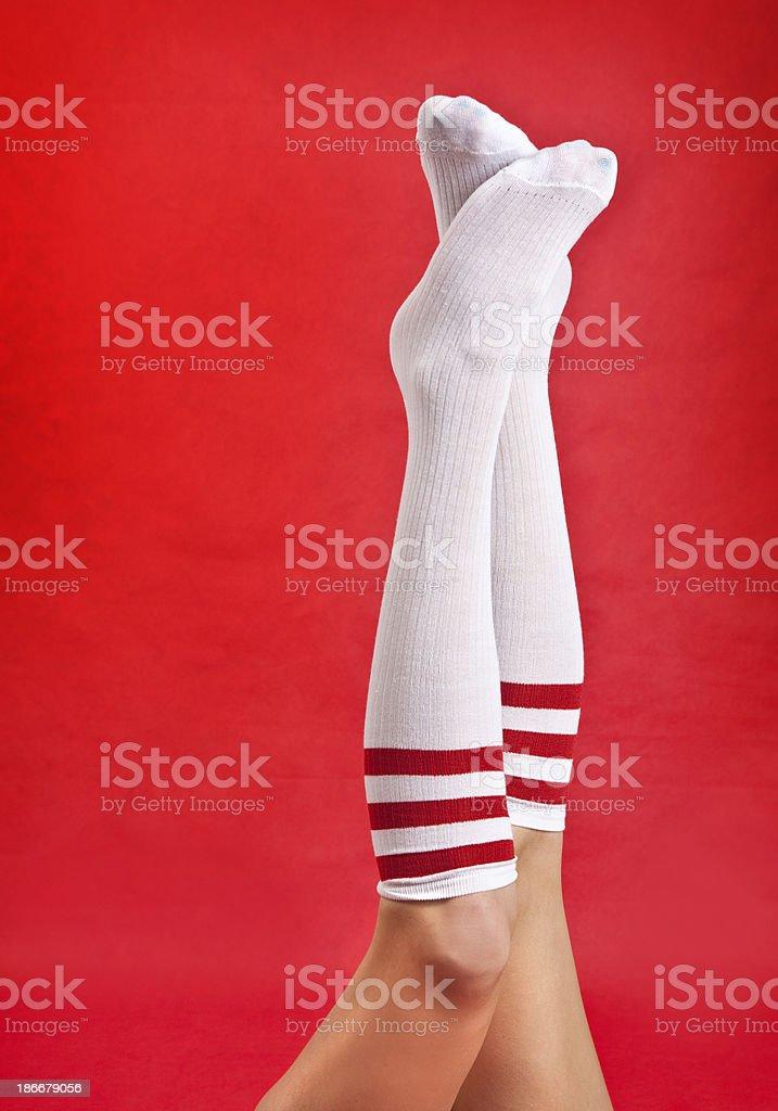 Woman's Legs Wearing Striped Knee Socks stock photo