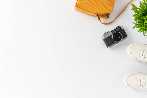 Woman's lifestyle background with camera photo, purse and sneakers. Travel concept. Flat lay stock photo
