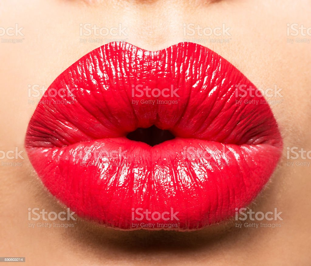 Woman's lips with red lipstick and  kiss gesture stock photo