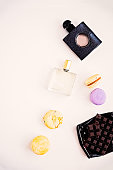 Woman's cosmetics, perfumes, natural oil, macaroons, dark chocolate. Beauty blog and social media flat lay on white. Spring mood, negative space