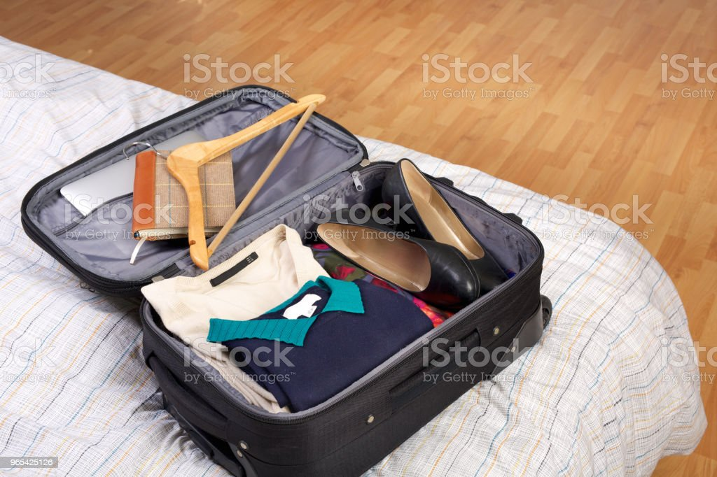 Woman's packed open black suitcase on top of a bed zbiór zdjęć royalty-free