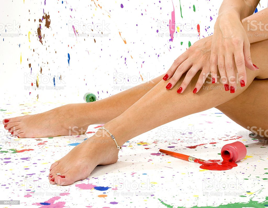 Woman's red nails with hands and legs on splattered canvas royalty-free stock photo