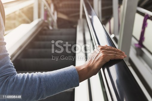 Woman's right hand on the escalator handrail on the train station