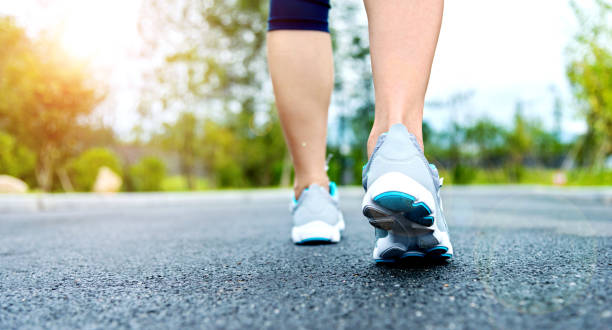 Woman's running shoes on asphalt road stock photo
