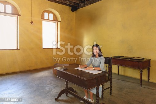 Womans signing a guest book with a pen and window light and shadow