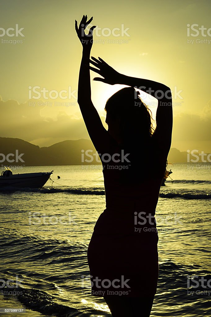 Womans silhouette posing at the beach on Zakyntos & hands stock photo