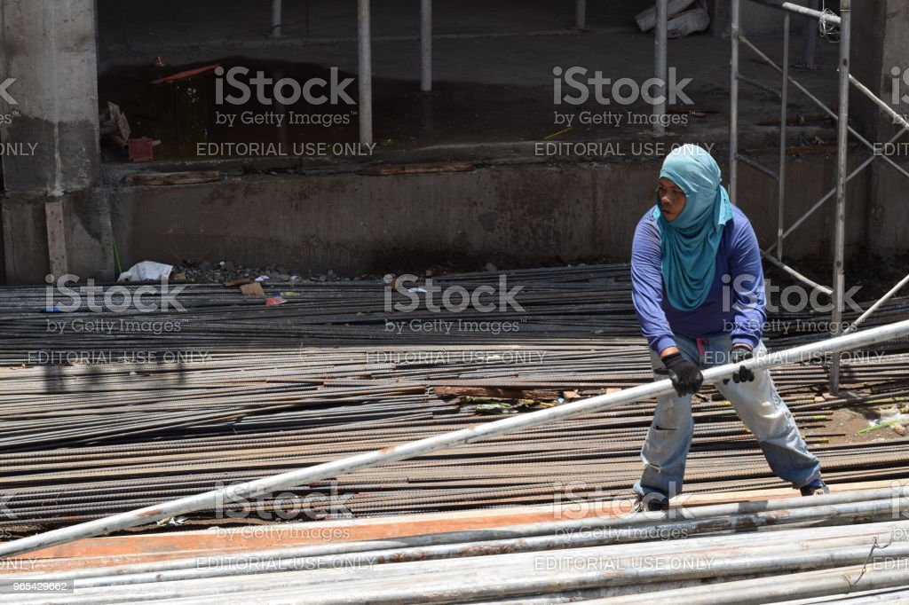 Woman's toil for a man's job zbiór zdjęć royalty-free