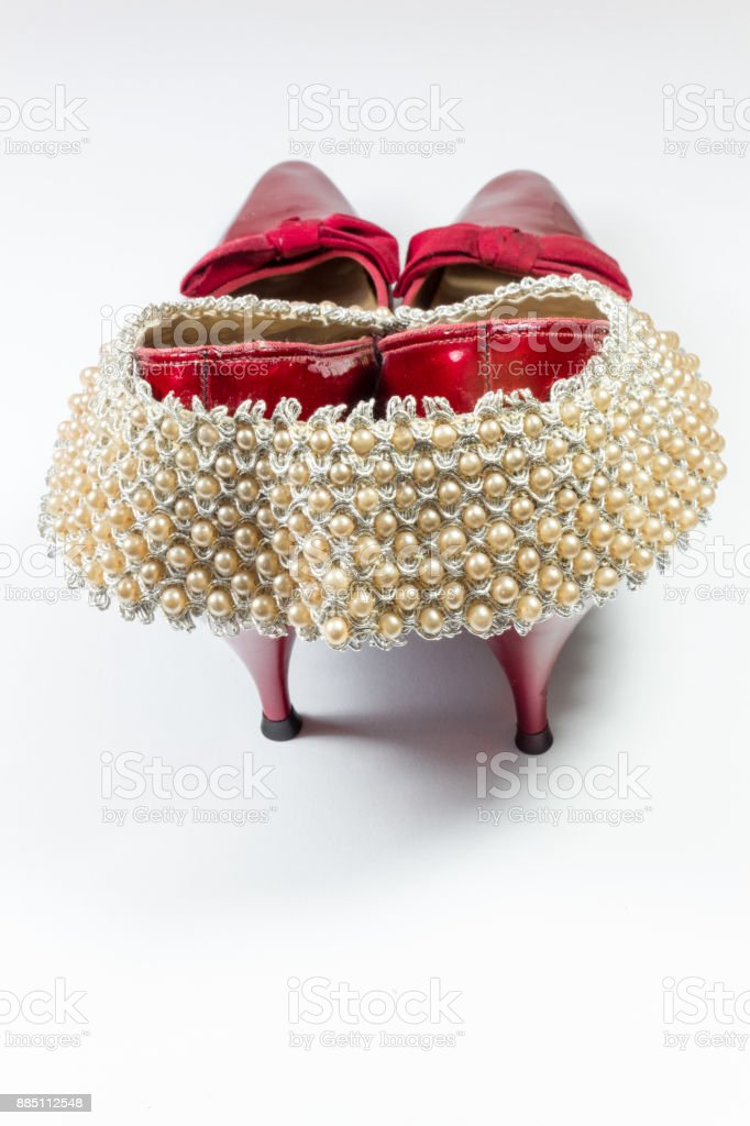 Woman's vintage faux pearl collar draped over vintage ruby red shoes, rear view, copy space stock photo