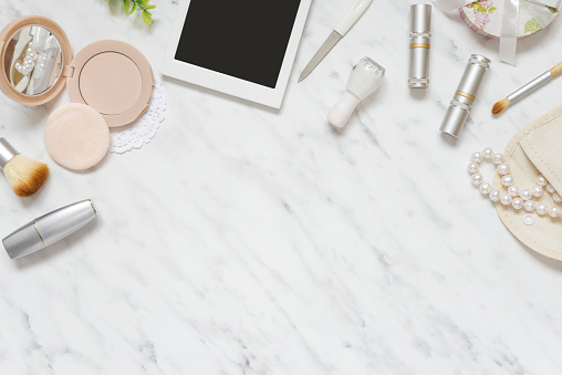 Woman's workplace with cosmetic and smartphone