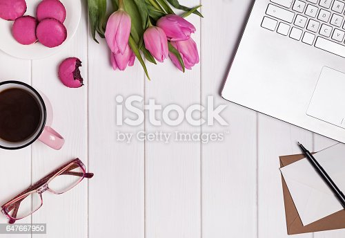 istock Woman's workplace with laptop, coffee pink tulips and macarons. 647667950