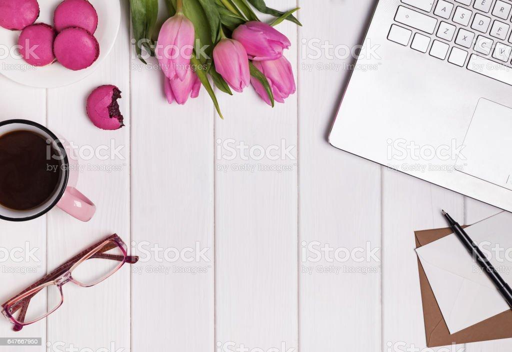 Local de trabalho a mulher com computador portátil, tulipas rosa café e macarons. - foto de acervo