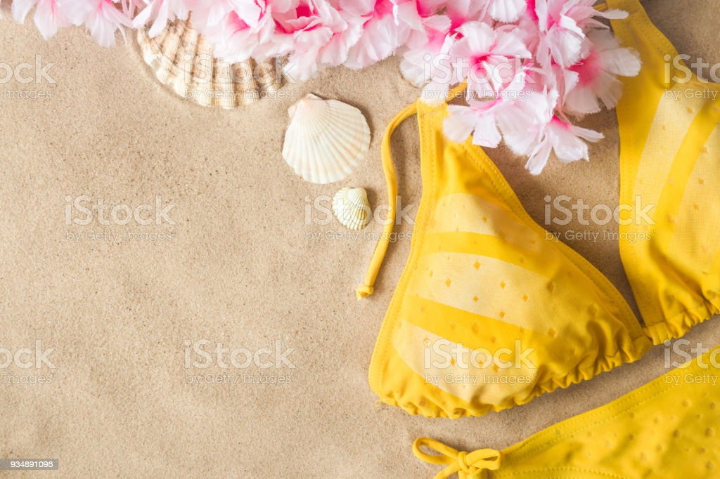 Woman's yellow swimsuit with seashells and hawaiian colorful flower necklace on sand. Hot, sunny day at the beach in summer. Sunbathing concept. Empty place for text. stock photo