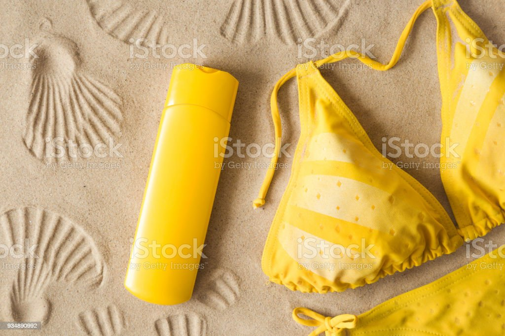 Woman's yellow swimsuit with sunscreen on sand with seashells imprints. Sunny day at the beach. Cares about skin protection in hot summer. Sunbathing concept. stock photo