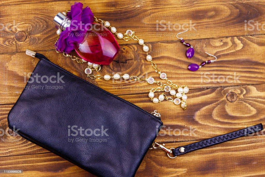 1cab6ac58510 Acessórios das mulheres no fundo de madeira. Saco de embreagem, frasco do  perfume,