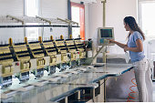 women  adjusting Automatic Embroidery Machine in Textile Factory