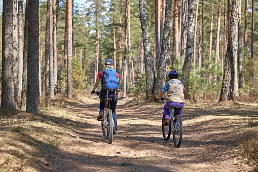 Women and boy biking on forest trails