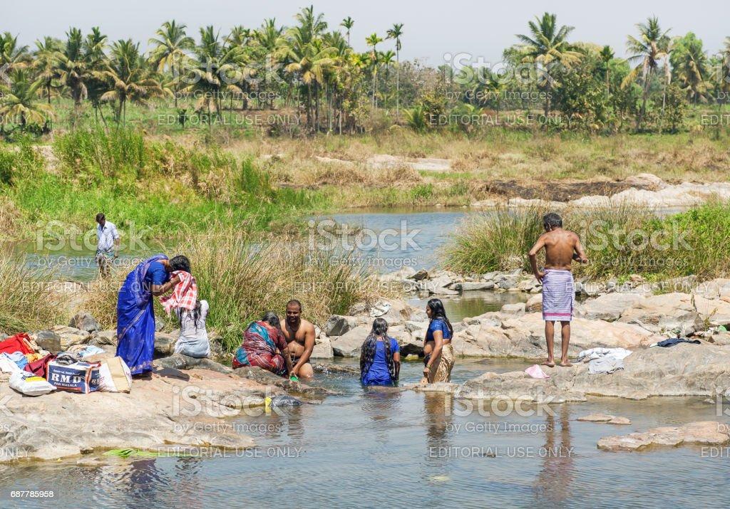 Frauen und Männer Baden und Wäsche in einem Fluss in der Nähe von einem indischen Dorf – Foto