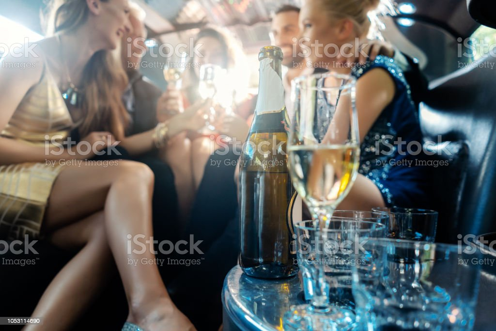 Women and men celebrating with drinks in a limousine car stock photo