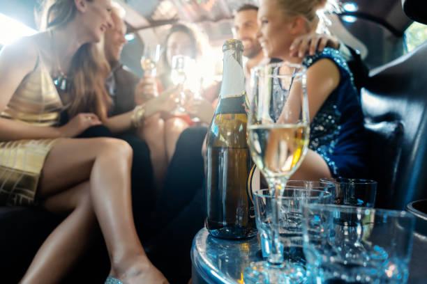 Frauen und Männer feiern mit Getränken in einem Auto limousine – Foto