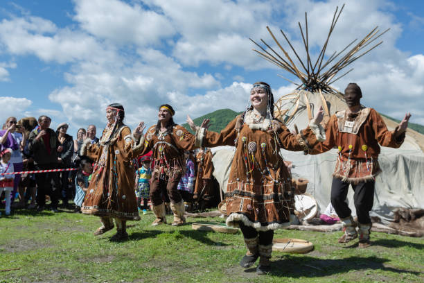 Women and men in national clothing indigenous inhabitants of Kamchatka expression dancing PETROPAVLOVSK CITY, KAMCHATKA PENINSULA, RUSSIA - JULY 11, 2015: Women and men in national clothing indigenous inhabitants of Kamchatka expression dancing near yaranga. Concert national folklore dance group on Fishermans Day kamchatka peninsula stock pictures, royalty-free photos & images